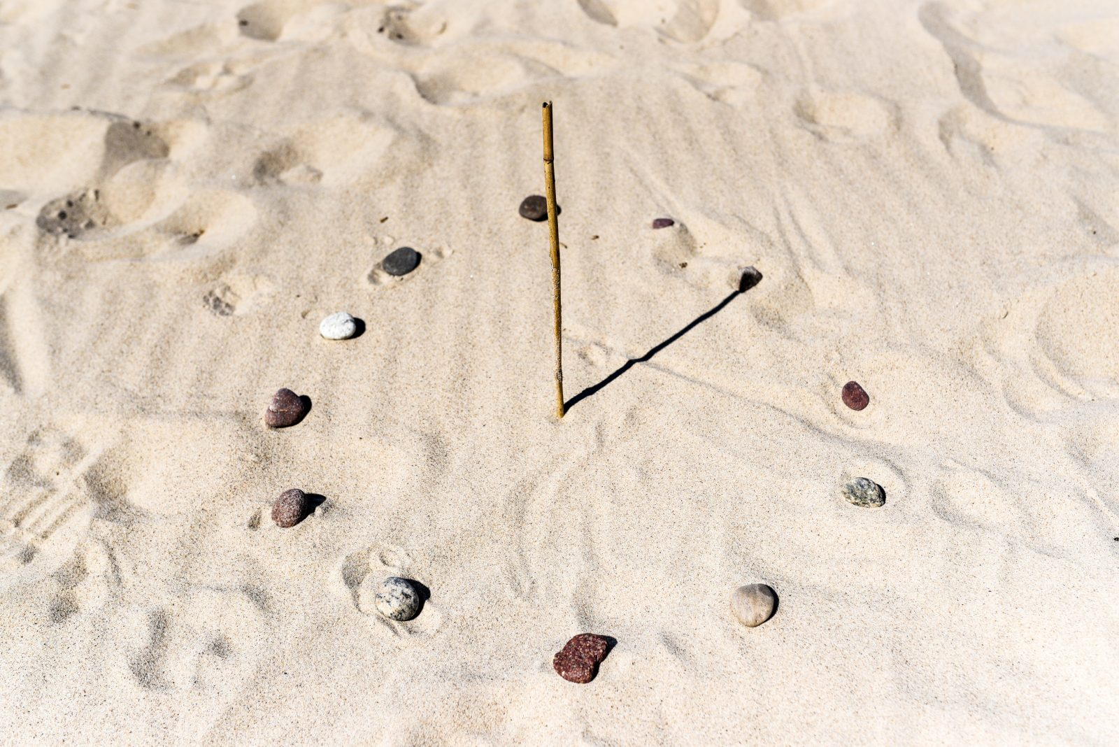 Sundial on the beach made of a stick and stones.