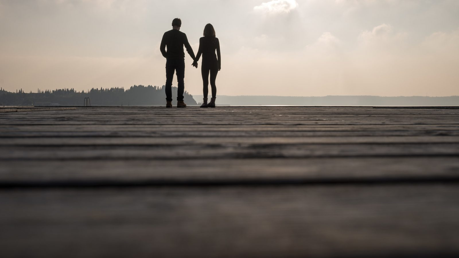 Silhouette of romantic couple holding their hands